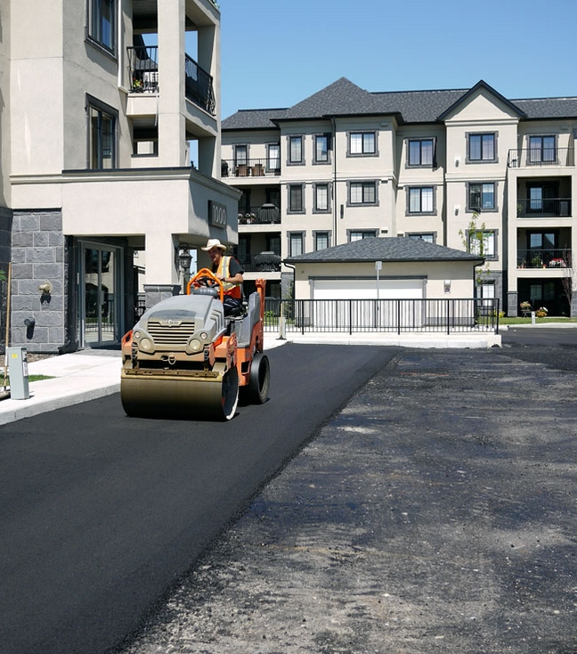 Photo of an Asphalt Roller Working at a Condominium Site