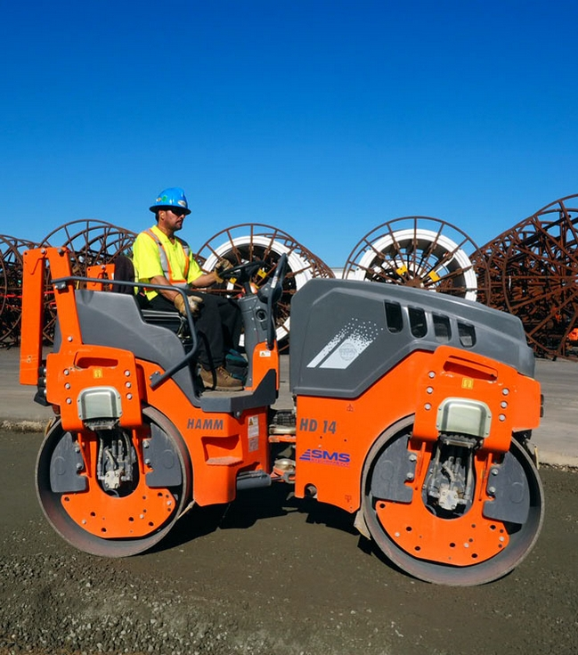 Photo of heavy-duty roller working on compacted concrete.